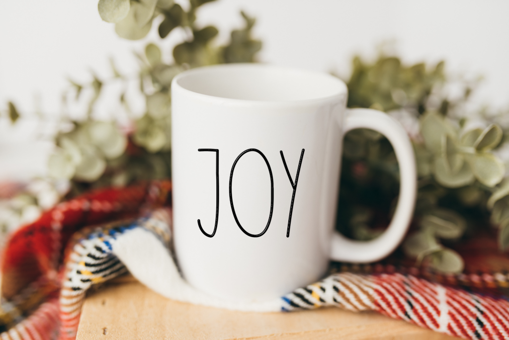 White mug with the text JOY on it.